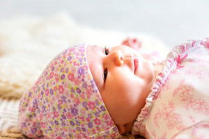 Newborn baby girl lying on her blanket