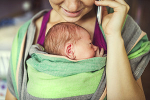 Newborn baby hold by mother in the baby wrap carrier. Mum calling at the phone.