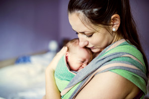 Newborn baby hold by mother in the baby wrap carrier.