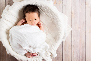 Newborn infant baby boy in a little basket