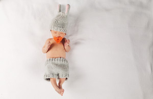 Newborn infant baby boy lying on a blanket in a bunny outfit
