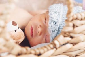 Newborn infant baby boy sleeping in a little basket