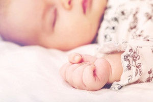 Newborn infant baby girl's clasped right hand