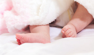 Newborn infant baby's feet sticking out from under her blanket