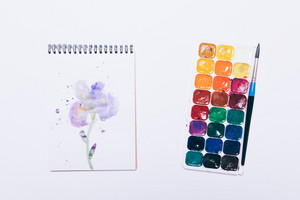 Notepad with drawing of a flower and watercolor on white table, top view