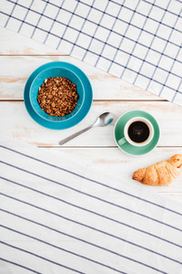 Oat cereals, cup of coffee, croissant with striped and plaid napkins on wooden background