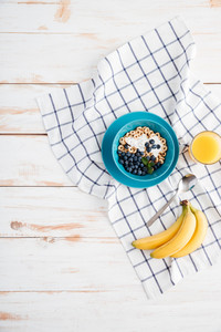 Oat cereals with berries and cream, cup of orange juice, bananas and plaid napkin on wooden background