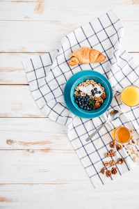 Oat cereals with berries and cream, cup of orange juice, croissant and plaid napkin on wooden background