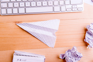 Office desk, paper airplane, crumpled paper balls. Flat lay. Studio shot on wooden background.