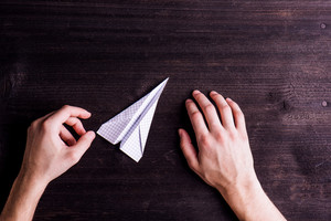Office desk with hands of unrecognizable man holding paper airplane. Flat lay. Workplace. Studio shot on dark wooden background.