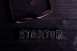 Office desk with start up sign made of cookie cutters. Flat lay. Workplace. Studio shot on wooden background. Copy space