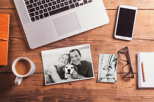 Office desk with various objects and black-and-white photos of senior couple. Studio shot on wooden background.