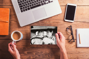 Office desk with various objects. Hands of unrecognizable man holding black and white picture of senior couple in love and cup of coffee. Studio shot on wooden background.