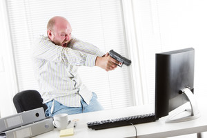 Office worker / businessman attack his computer with a gun.