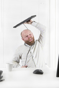 Office worker / businessman strangle himself with his keyboard cable