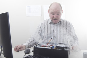 Office worker / businessman with computer problems. Smoke.