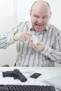 Office worker taking drugs and has a gun on his desk.