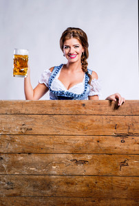 Oktoberfest. Beautiful young woman in traditional bavarian clothes standing behind brown wooden planks, holding a mug of beer, copy space. Studio shot on gray background.