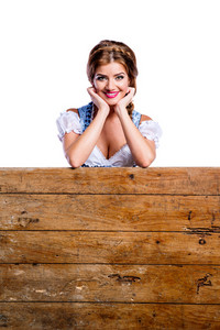 Oktoberfest. Beautiful young woman in traditional bavarian clothes standing behind brown wooden planks, supporting chin, copy space. Studio shot on white background, isolated.