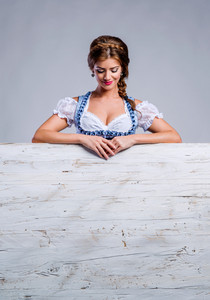 Oktoberfest. Beautiful young woman in traditional bavarian clothes standing behind white wooden planks, copy space. Studio shot on gray background.