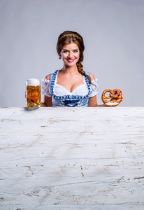 Oktoberfest. Beautiful young woman in traditional bavarian clothes standing behind white wooden planks, holding a mug of beer and pretzel, copy space. Studio shot on gray background.