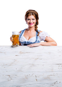 Oktoberfest. Beautiful young woman in traditional bavarian clothes standing behind wooden planks, holding a mug of beer, copy space. Studio shot on white background, isolated.