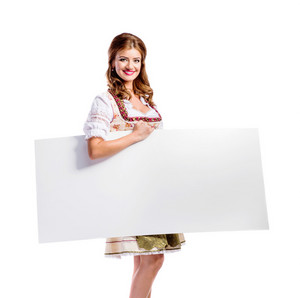 Oktoberfest. Beautiful young woman in traditional bavarian dress, holding empty white board. Copy space. Studio shot on white background, isolated.