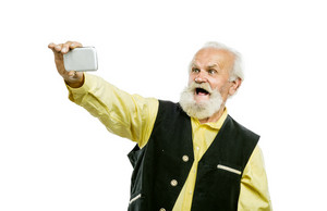 Old active bearded man taking selfie with mobile phone isolated on white background