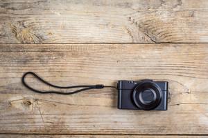 Old camera laid on wooden desk background.