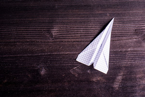 Old dark wooden board background, plank with texture, paper airplane, empty copy space