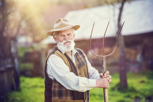 Old farmer with pitchfork taking a break from work