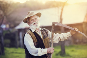 Old farmer with scythe taking a break from mowing the grass
