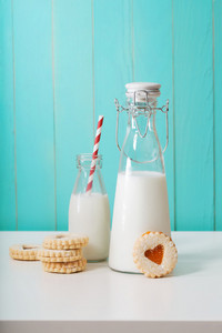 Old fashion milk jars with heart shaped cookies on pastel blue background