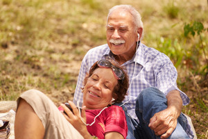 Old people, senior couple, elderly man and woman in park. Grandpa and grandma listening to song, music with mp3 player