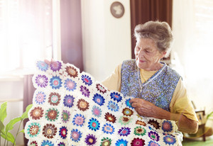 Old woman is knitting a blanket inside in her living room