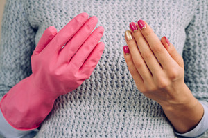 One hand in rubber glove for cleaning, the other with bright manicure. A woman in a gray sweater showing hands.
