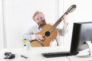 One happy office worker drinking, playing guitar and smoking in his office.