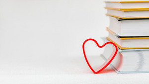 One heart shape lean on books pile placed on the white surface