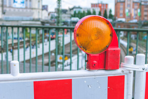 Orange construction warning street barrier light on barricade. Road construction on the streets of European cities. Germany. Hamburg