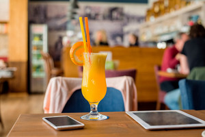 Orange drink, tablet, smart phone laid on table in city cafe