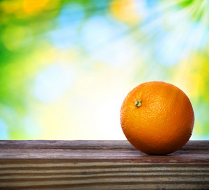 Orange on wooden table over green shiny background