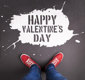Original Valentine's Day love concept with red sneakers and chalk drawn Happy Valentine's Day title.