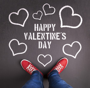 Original Valentine's Day love concept with red sneakers and chalk drawn heart symbol.