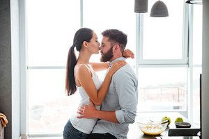 Сouple cuddling and kiss in kitchen. side view