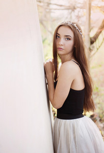 Outdoor portrait of beautiful girl posing by the old house