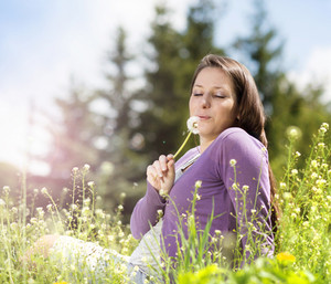Outdoor portrait of beautiful pregnant woman blowing to dandelion in green meadow