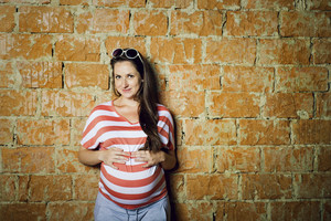 Outdoor portrait of beautiful pregnant woman holding her belly, brick wall in background