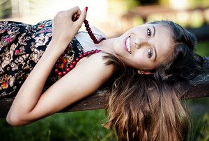 Outdoor portrait of beautiful teenage girl lying down on a bench in green sunny park