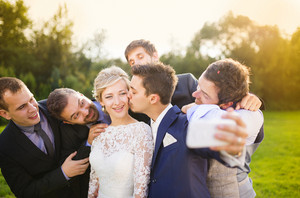 Outdoor portrait of beautiful young bride with groom and his friends taking selfie