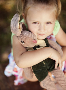 Outdoor portrait of cute little girl holding her toy